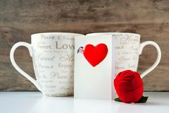 Valentine gift box with greeting card and two cups. On wooden background. Indoors close-up Royalty Free Stock Photos