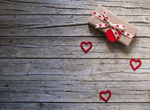 Valentine gift box and heart shape tag on wooden board Royalty Free Stock Photography