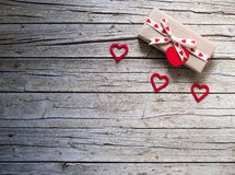 Valentine gift box and heart shape tag on wooden board Royalty Free Stock Images