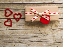 Valentine gift box and heart shapes on wooden board Stock Image