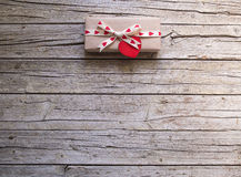 Valentine gift box and heart tag on wooden board Royalty Free Stock Images