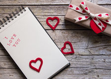Valentine gift box, notebook and red heart shape tag on wooden b. Oard Stock Photography