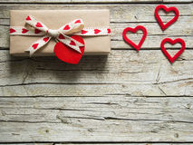 Valentine gift box and red heart on wooden board. Valentine gift box and red heart shapes, on wooden board Royalty Free Stock Photo
