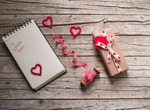 Valentine gift box, ribbon, notebook and heart shape tag on. Valentine gift box, ribbon, notebook and red heart shape tag on wooden board Royalty Free Stock Photos