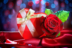 Valentine gift box and rose flower on red silk Royalty Free Stock Photos