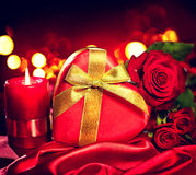 Valentine gift box and rose flower on red silk Royalty Free Stock Images