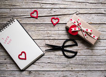 Valentine gift box, scissor, notebook and heart shape tag on. Valentine gift box, scissor, notebook and red heart shape tag on wooden board Royalty Free Stock Photo