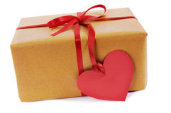 Valentine gift, brown paper parcel, red heart shape gift tag isolated on white Royalty Free Stock Image
