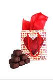 Valentine Gift and Chocolates. Chocolates and a gift bag with red wrapping Royalty Free Stock Images