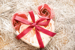 Valentine gift flowers red ribbon. Little valentine gift with flowers and red ribbon on silver Stock Photos