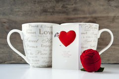 Valentine gift with greeting card and two cups. Valentine gift box with greeting card and two cups on wooden background. Close-up Stock Photography