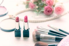 Valentine Gift. Makeup cosmetics tools background and beauty cosmetics, products. And facial cosmetics package lipstick, eyeshadow with pink rose, Pearl Stock Images