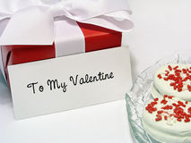 Valentine Gift with Tag. Gift box wrapped in red paper, tied with a white ribbon, with a Valentine greeting tag Stock Image