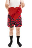 Valentine Gift For You. Humorous photo of a man in heart boxers and black socks holding a box of Valentine candy. Isolated on white stock image