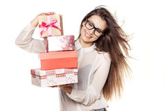Valentine gifts. Beautiful young woman with glasses and windy hair posing with several gifts royalty free stock image