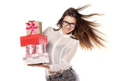 Valentine gifts. Beautiful young woman with glasses and windy hair posing with several gifts royalty free stock photo