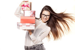Valentine gifts. Beautiful young woman with glasses and windy hair posing with several gifts royalty free stock photography