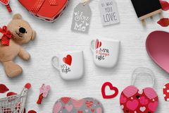 Valentine`s gifts on a white wooden background. Valentine gifts on a white wooden background. Gifts, cups, clips, teddy bear, inscriptions. Top view Stock Photos