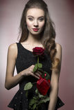 Valentine girl with rose. Young, beautiful, elegant girl with lice make up in black dess is holding valentine's present like rose and heart stock photos