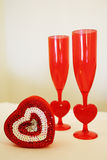 Valentine Glasses and Box. Two unique valentine glasses with heart-shaped stems and a heart-shaped box of chocolates Royalty Free Stock Photos