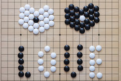 Valentine Go game. Two hearts of black and white stones are on a goban Stock Photography