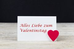 Valentine greeting card on wooden table with text Alles Liebe zum Valentinstag, written in German, which means Happy Valentine d. Valentine greeting card on royalty free stock photo