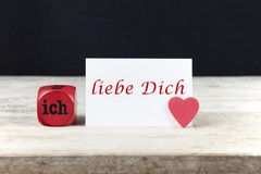 Valentine greeting card on wooden table with text Ich liebe Dich, written in German, which means I love you.  stock image