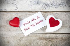 Valentine greeting card on wooden table with text written in spanish Feliz dia de San Valentin, which means Happy Valentine`s day. Valentine greeting card on stock photo