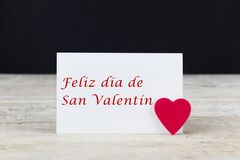 Valentine greeting card on wooden table with text written in Spanish Feliz dia de San Valentin, which means Happy Valentines day.  stock image