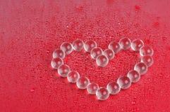 Valentine-hartsymbool op de rode natte achtergrond Stock Foto's