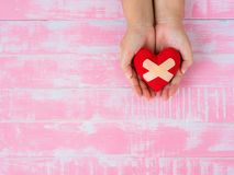 Valentine, health, medicine and charity concept.  heart on aging. Kid hand support Royalty Free Stock Image