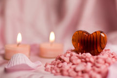Valentine heart. A detail of a transparent heart of red glass with stripes on a pile of little pink stones, two burning candles and flower petals Royalty Free Stock Photo