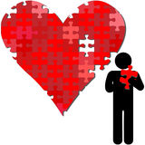Valentine heart puzzle piece in arms of person Stock Image