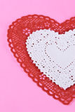 Valentine heart shaped doilies on pink paper background Royalty Free Stock Photography