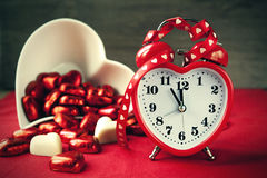 Valentine heart shaped red love clock with chocolates. Time for sweet love Royalty Free Stock Image