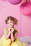 Valentine heart to make your fingers. Pretty girl child 6 years old in a yellow dress. Baby in Rose quartz room Stock Photos