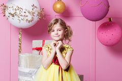 Valentine heart to make your fingers. Pretty girl child 6 years old in a yellow dress. Baby in Rose quartz room Stock Photo
