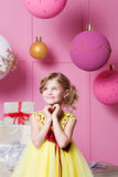 Valentine heart to make your fingers. Pretty girl child 6 years old in a yellow dress. Baby in Rose quartz room Royalty Free Stock Photography