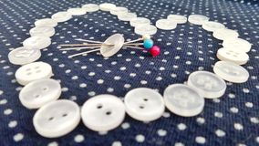 Valentine Heart white buttons and colourful pin on blue and white polka dot cloth Royalty Free Stock Image
