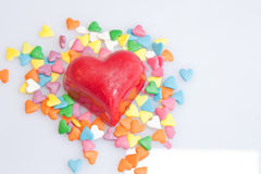Valentine Hearts. A red-shelled, heart-shaped chocolate surrounded by small candy hearts Royalty Free Stock Image