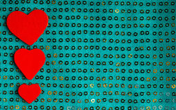 Valentine hearts on green sequins material Stock Photos