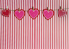 Valentine Hearts Hanging From Twine em um fundo listrado vermelho imagens de stock royalty free