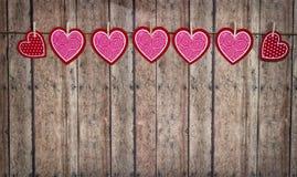 Valentine Hearts Hanging From Twine en un fondo de madera Foto de archivo libre de regalías