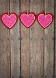 Valentine Hearts Hanging From Twine su un fondo di legno Immagine Stock Libera da Diritti