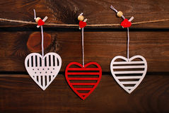 Valentine hearts hanging on wooden background Stock Photography
