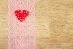 Valentine hearts on lace pattern fabric,wood background Stock Photography
