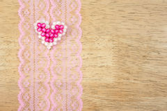 Valentine hearts on lace pattern fabric,wood background Royalty Free Stock Image