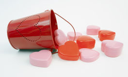 Valentine Hearts. Pink and red Valentine hearts spilling from red pail with heart design stock photos