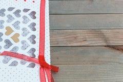 Valentine& x27 ; jour de s carte blanche avec les coeurs coupés et enveloppe d'or sur la table en bois, affichage de produit Photos stock