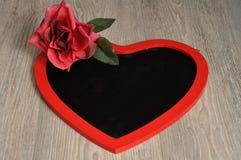 Valentine& x27 ; jour de s Un tableau noir de forme de coeur avec une rose rouge Photos libres de droits